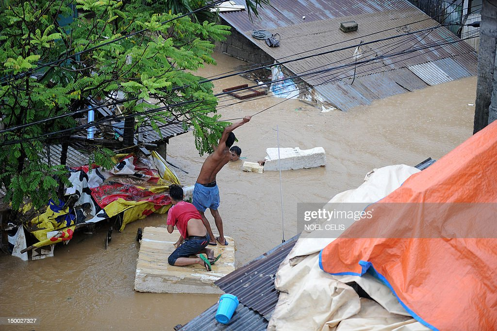 Residents travel along a flooded street on a flotation device towards their house near a river that overflowed caused by torrential rains in San Mateo, Rizal, suburban Manila on August 9, 2012. Philippine authorities appealed on August 9 for help in getting relief to two million people affected by deadly floods in and around the capital, warning that evacuation centres were overwhelmed.