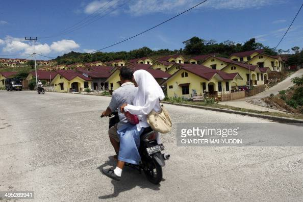 Residents travel on motorcycle at the resettlement area for tsunami victims in Banda Aceh on April 16 2009 Indonesia's tsunami reconstruction agency...