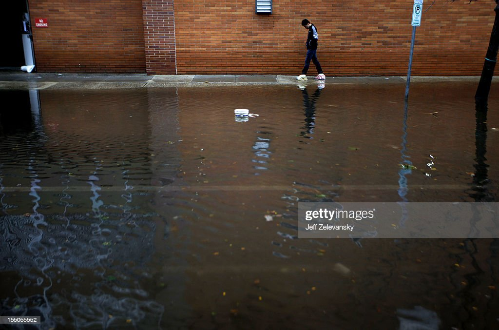 Residents traverse flooded streets as clean-up operations begin on October 31, 2012 in Hoboken, New Jersey. Known as the Mile Square City, the low-lying neighborhoods suffered deep flooding resulting from the storm surge associated with Hurricane Sandy.