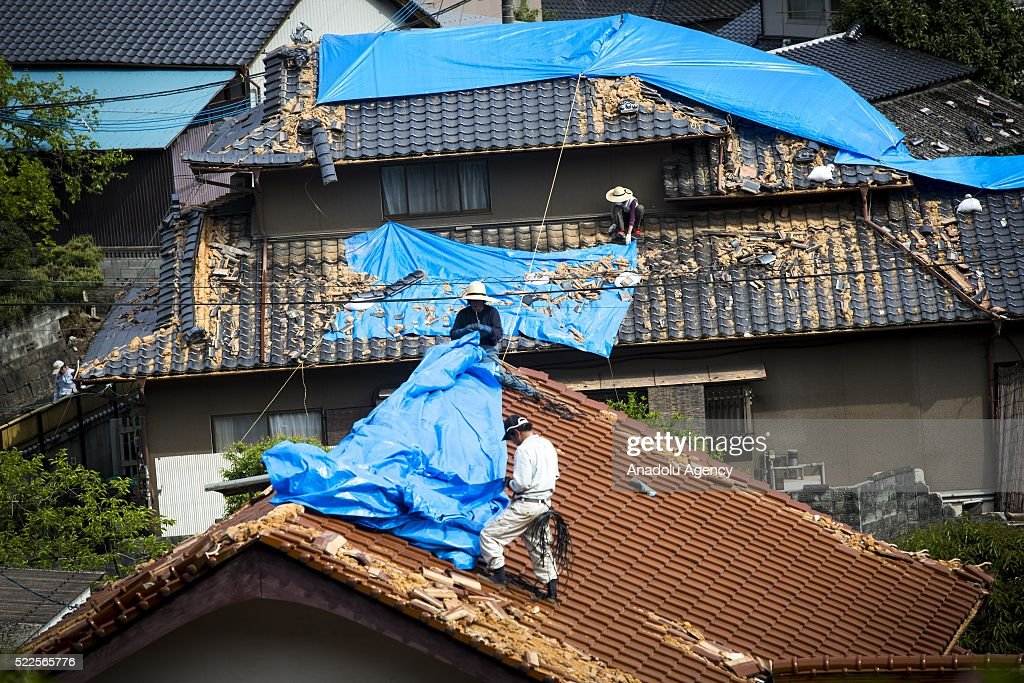 Residents try to fix the destroyed roof of houses on April 20 2016 in Mashiki town Kumamoto Japan At least 41 people were killed and over 180000...