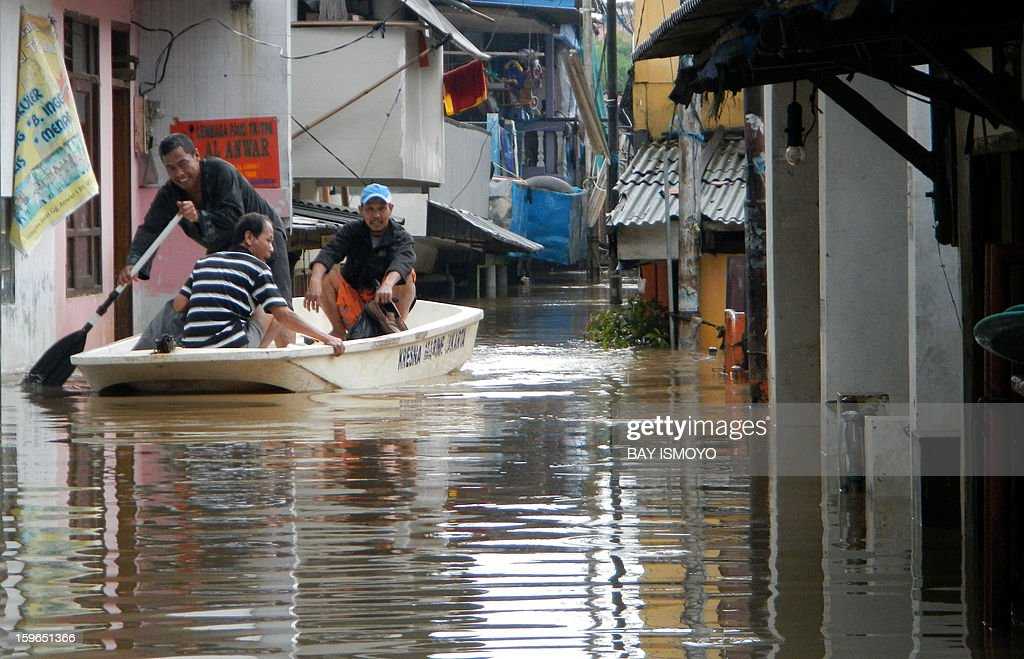 Residents use a boat to retrieve belongings from their flooded homes in Jakarta on January 18, 2013. Floods in Indonesia's capital Jakarta have left at least 11 people dead, authorities said on January 18 as murky brown waters submerged parts of the city's business district, causing chaos for a second day. AFP PHOTO / Bay ISMOYO