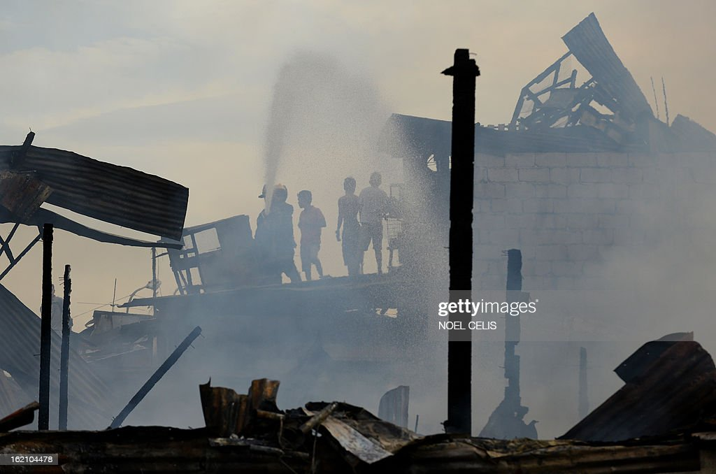 Residents use a fireman's hose to extinguish a fire that engulfed a slum area in Manila on February 19, 2013. Almost 100 houses were destroyed, leaving 200 residents homeless and three dead bodies were found according to a local media report.