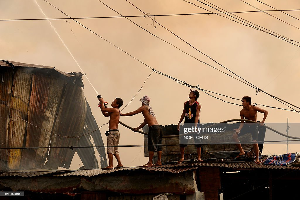 Residents use a fireman's hose to extinguish a fire that engulfed a slum area in Manila on February 19, 2013. Almost 100 houses were destroyed, leaving 200 residents homeless and three dead bodies were found according to a local media report. AFP PHOTO/NOEL CELIS