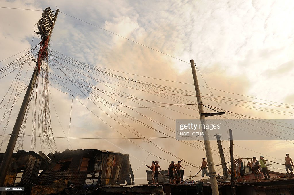 Residents (bottom C) use a firemen's hose to extinguish a fire that engulfed a slum area in Manila on February 19, 2013. Almost 100 houses were destroyed, leaving 200 residents homeless and three dead bodies were found according to a local media report. AFP PHOTO/NOEL CELIS