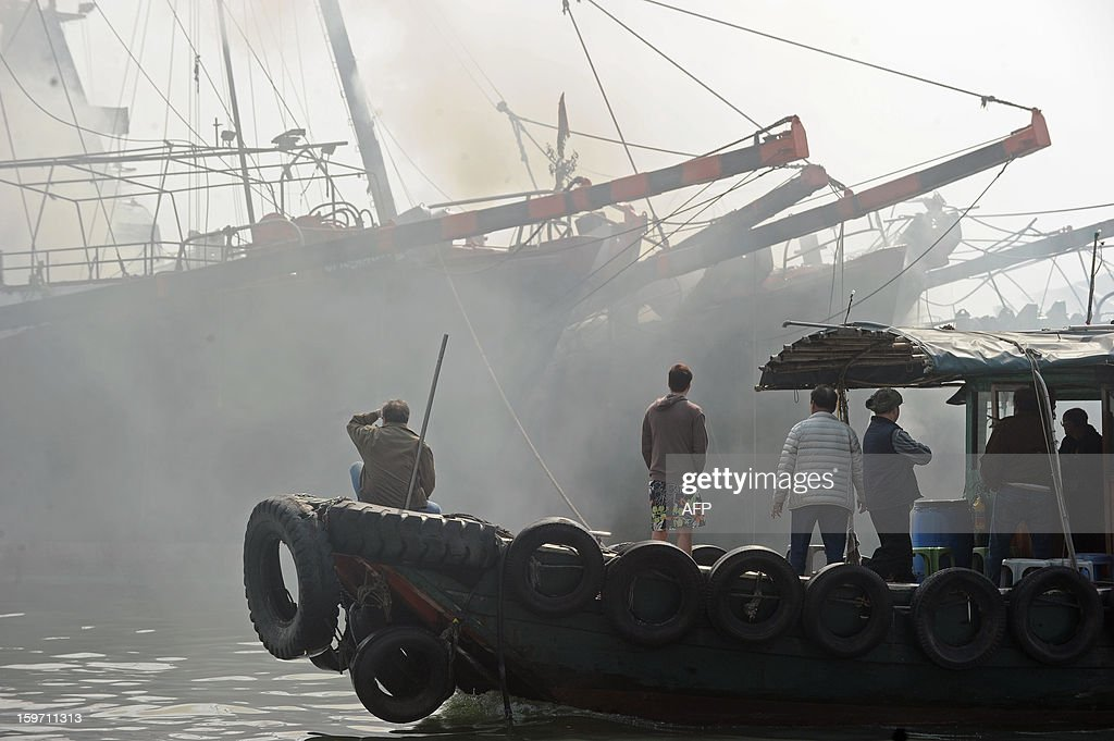 Residents use a local taxi ferry (front) to look at smoke billowing from two burnt fishing vessels (back R) after they caught fire in Hong Kong on January 19, 2013. There were no initial reports of injuries during the incident, which took place in a crowded typhoon shelter.