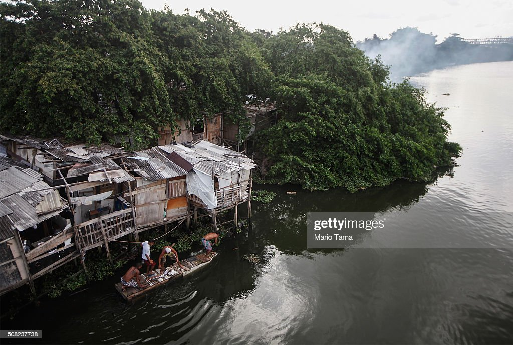 Residents use a makeshift boat as they prepare to attempt to recover items from a nearby fire which destroyed many wooden makeshift homes along the polluted Capibaribe River on February 3, 2016 in Recife, Pernambuco state, Brazil. Officials say as many as 100,000 people may have already been exposed to the Zika virus in Recife, many from poorer areas, although most never develop symptoms. The state with the most cases is Pernambuco, whose capital is Recife, and is being called the epicenter of the outbreak. In the last four months, authorities have recorded thousands of cases in Brazil in which the mosquito-borne Zika virus may have led to microcephaly in infants. Microcephaly results in an abnormally small head in newborns and is associated with various disorders.