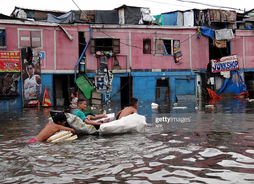 Residents use a makeshift flotation device as they cross a flooded street in Manila on August 8, 2012, after torrential rains inundated most of the capital. More than 800,000 people in and around the Philippine capital battled deadly floods as more rain fell, with neck-deep waters trapping slum dwellers and the wealthy elite on rooftops.
