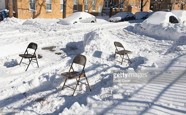 Residents use folding chairs to reserve a parking spot on the street after digging a car out from the snow on February 2 2015 in Chicago Illinois...