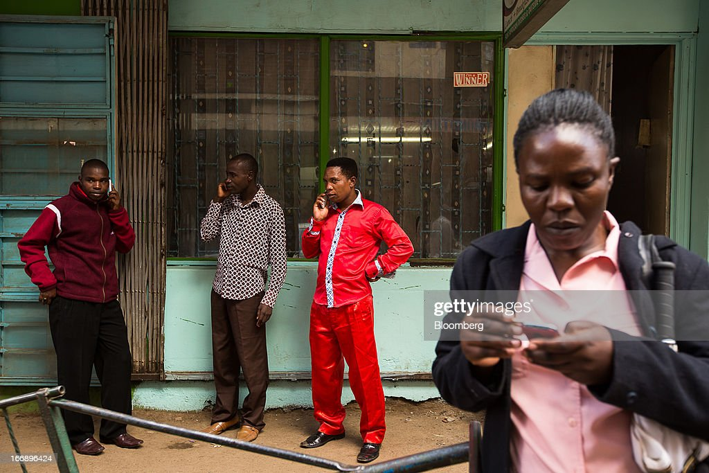 Residents use mobile handsets on a street in Nairobi, Kenya, on Wednesday, April 17, 2013. Though only 23 percent of houses there have electricity and just 9 percent of roads are paved, mobile-phone penetration is 75 percent in the country, up from 5 percent in 2003. Photographer: Trevor Snapp/Bloomberg via Getty Images