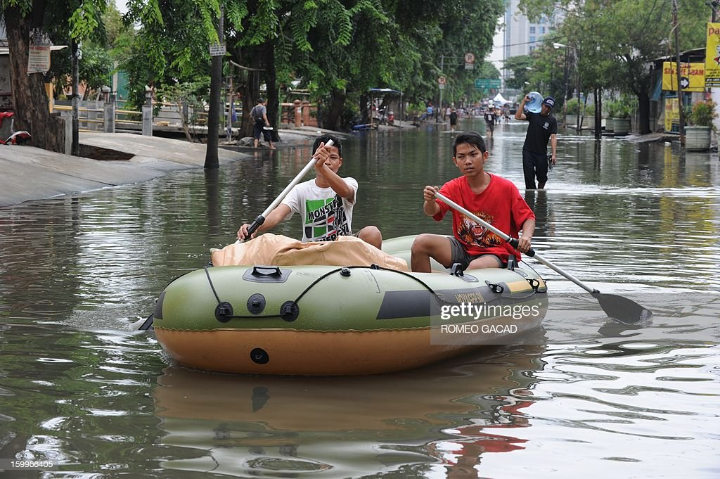 Residents use rubber boats to ferry goods in a flooded neighborhood in Jakarta on January 24, 2013. Indonesia's National Disaster Mitigation Agency (BNPB) said more than 30,000 people were displaced while 20 people died during the widespread flooding that hit Jakarta as the weather bureau forecast more rains in the coming days. AFP PHOTO / ROMEO GACAD