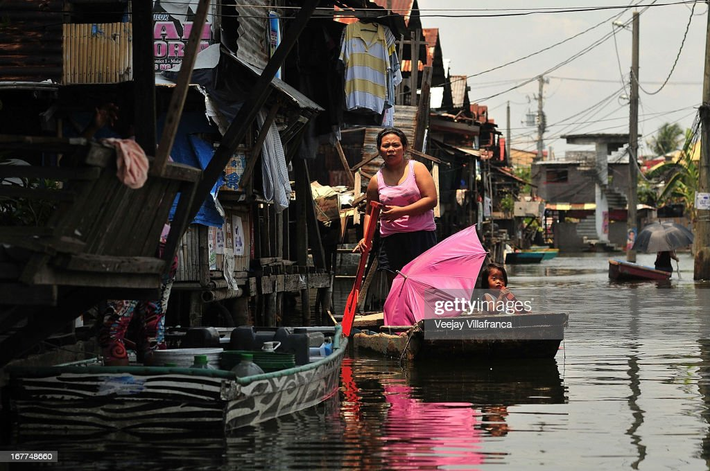 Residents uses makeshift boats to get around in Artex Compound in Malabon City on April 28, 2013 in Manila, Philippines. The residents of the former textile compound had to adjust their daily lives after flood waters submerged their low-lying village in 2004.