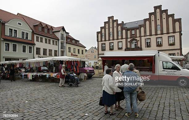 Residents visit the weekly market 23 August 2007 at the market square in Muegeln eastern Germany where eight Indians were injured in an attack During...