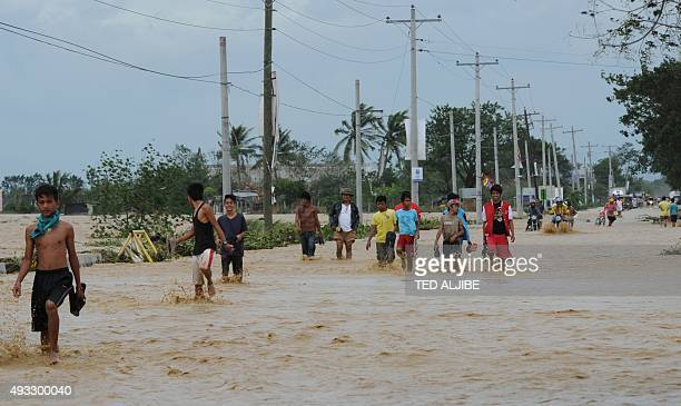 Residents wade through a flooded highway in Santa Rosa town Nueva Ecija province north of Manila on October 19 a day after typhoon Koppu hit Aurora...
