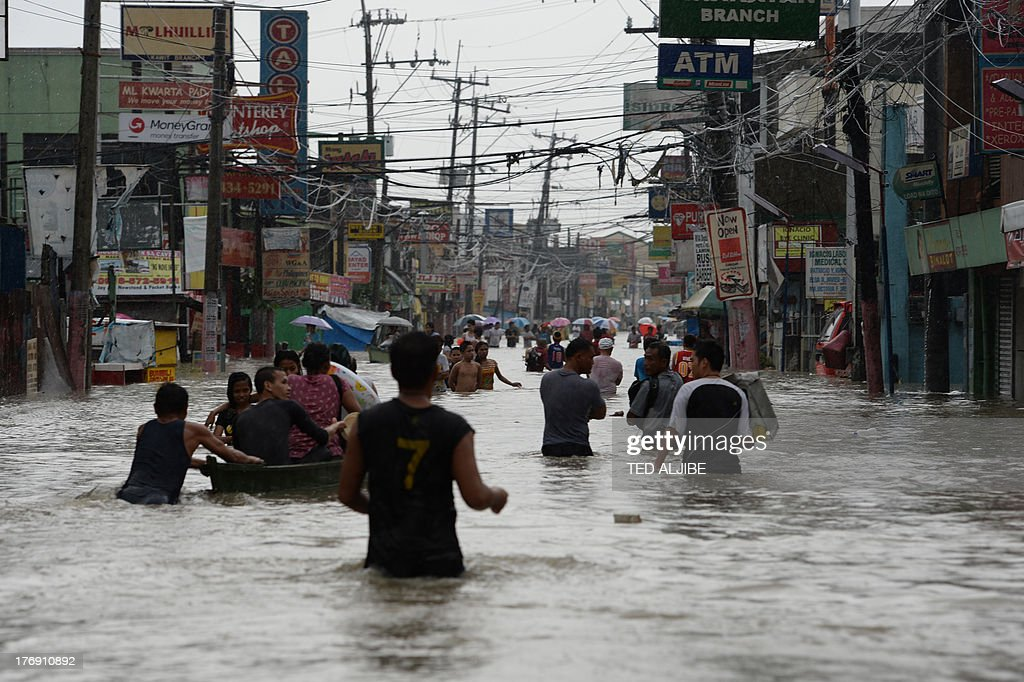 Residents wade through a flooded street in Cavite, southwest of Manila on August 19, 2013. Torrential rain paralysed large parts of the Philippine capital August 19, as neck-deep water swept through homes, while floods in northern farming areas claimed at least one life.