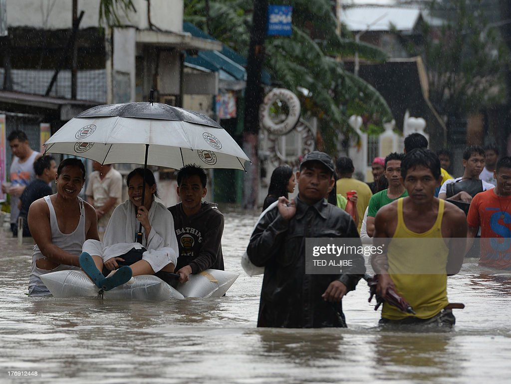 Residents wade through a flooded street in Cavite, southwest of Manila on August 19, 2013. Torrential rain paralysed large parts of the Philippine capital August 19, as neck-deep water swept through homes, while floods in northern farming areas claimed at least one life. AFP PHOTO/TED ALJIBE