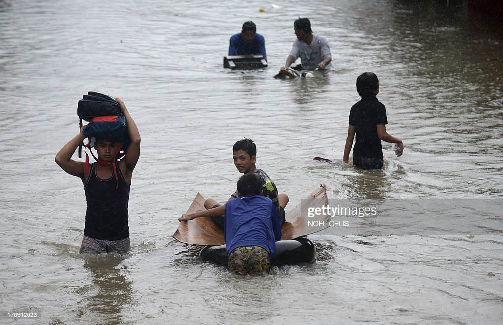 Residents wade through a flooded street in Manila on August 19, 2013. At least three people have died in the Philippines after torrential rain engulfed parts of the main island of Luzon including Manila where neck-deep water swept through homes forcing thousands into emergency shelters.