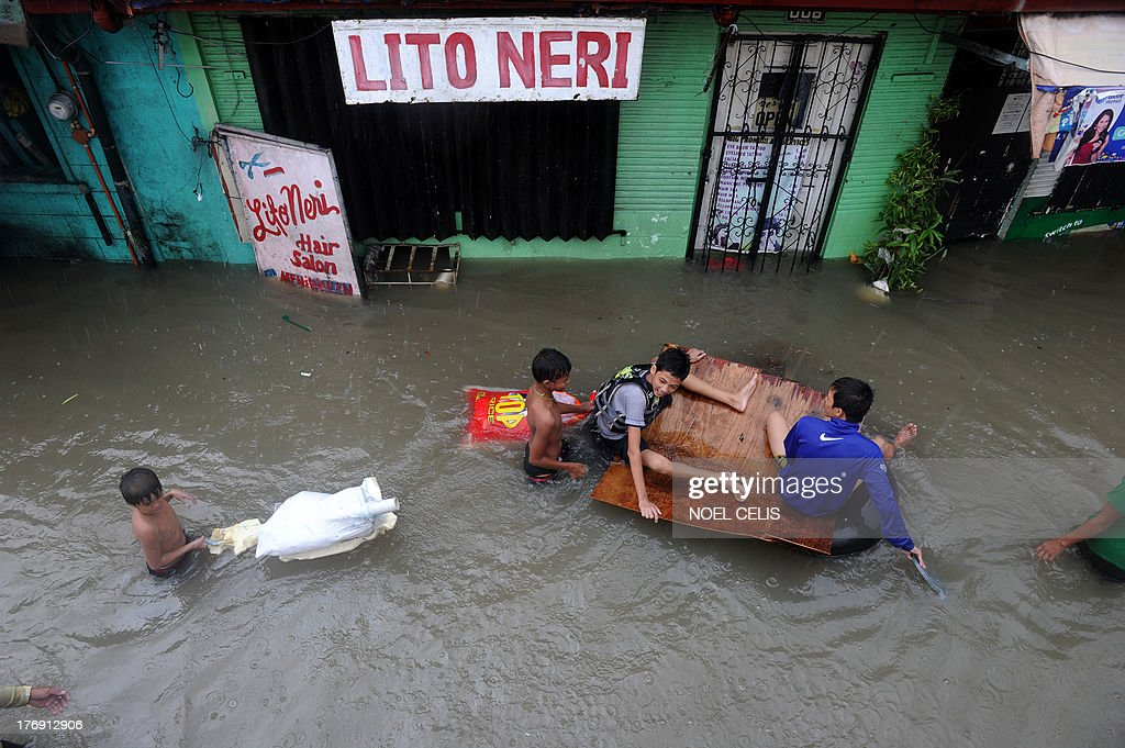 Residents wade through a flooded street in Manila on August 19, 2013. At least three people have died in the Philippines after torrential rain engulfed parts of the main island of Luzon including Manila where neck-deep water swept through homes forcing thousands into emergency shelters. AFP PHOTO/NOEL CELIS