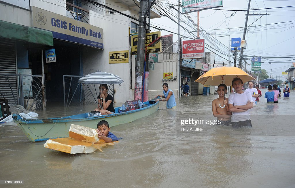Residents wade through a flooded street while others ride on a wooden boat in Cavite, southwest of Manila on August 19, 2013, after their houses (back) were submerged by flood waters due to heavy rains exacerbated by Tropical Storm Trami. Torrential rain paralysed large parts of the Philippine capital August 19, as neck-deep water swept through homes, while floods in northern farming areas claimed at least one life.