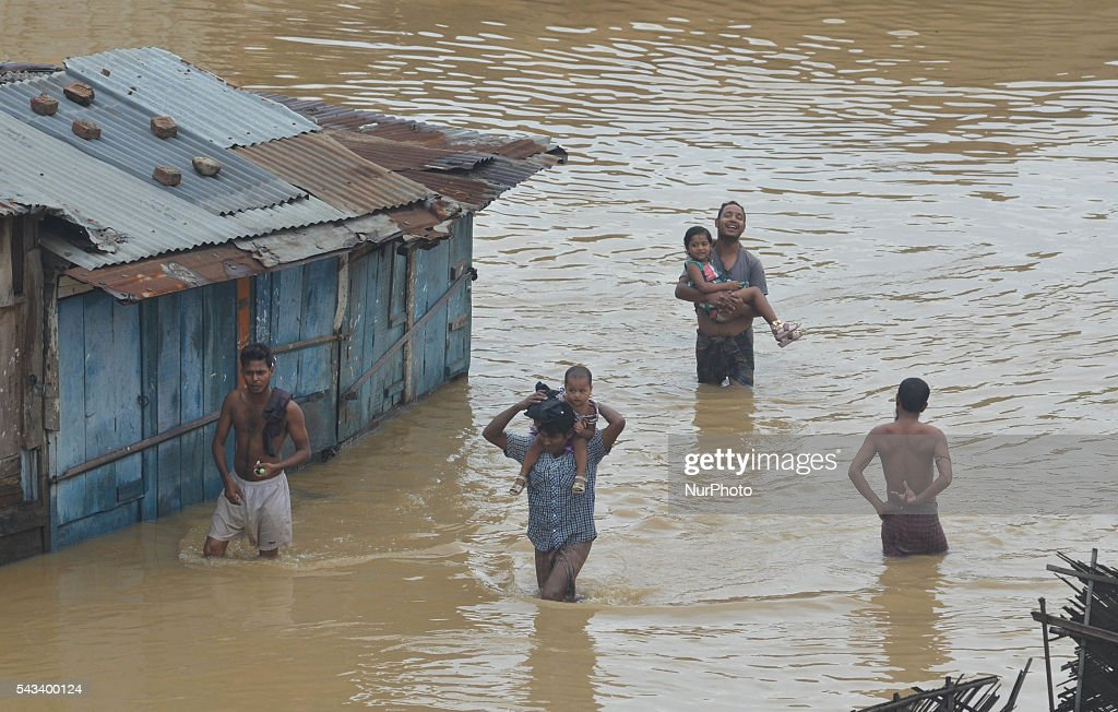 Residents wade through flood water after a heavy monsoon rain in Dimapur, India north eastern state of Nagaland on Tuesday, June 28, 2016. Thousands of people were render homeless after heavy monsoon rain in the state.