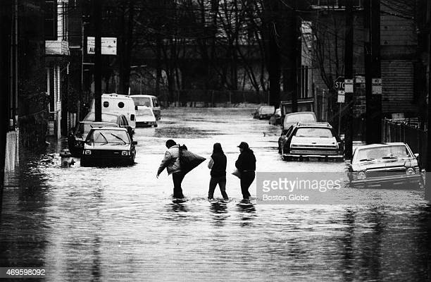 Residents wade through flood water from the Merrimack River carrying their belongings down Holly Street in Lawrence Mass on April 7 1987 Hundreds of...