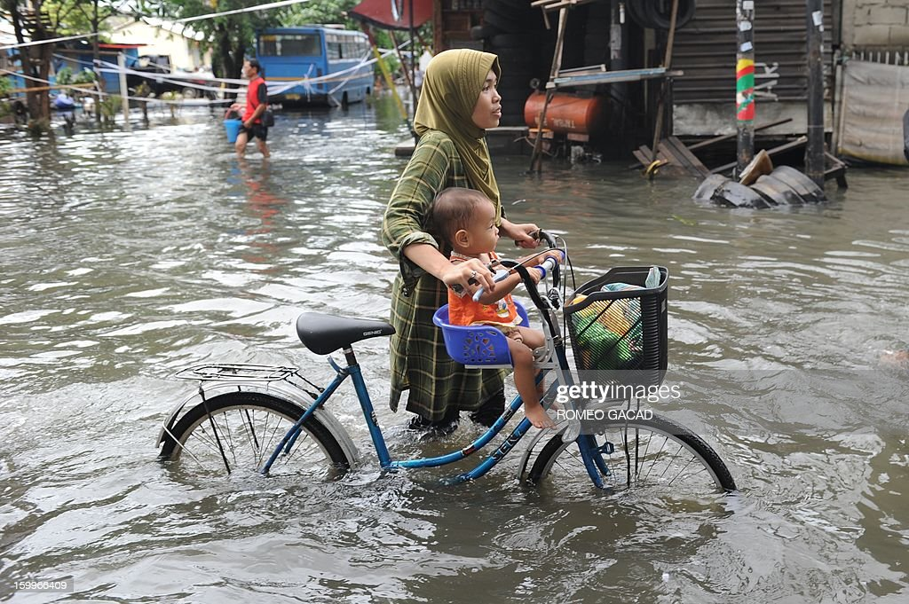 Residents wade through flooded neighborhood to reach relief distribution centers in Jakarta on January 24, 2013. Indonesia's National Disaster Mitigation Agency (BNPB) said more than 30,000 people were displaced while 20 people died during the widespread flooding that hit Jakarta as the weather bureau forecast more rains in the coming days. AFP PHOTO / ROMEO GACAD