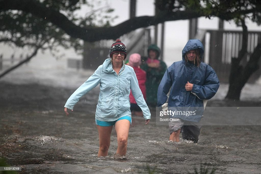 Residents wade through floodwater as they survey damage to the town resulting from Hurricane Irene on August 27, 2011 in Kill Devil Hills, North Carolina. Hurricane Irene hit Dare County, which sits along the Outer Banks and includes the vacation towns of Nags Head, Kitty Hawk and Kill Devil Hills, as a category one hurricane around mid-day today causing wind damage and flooding.