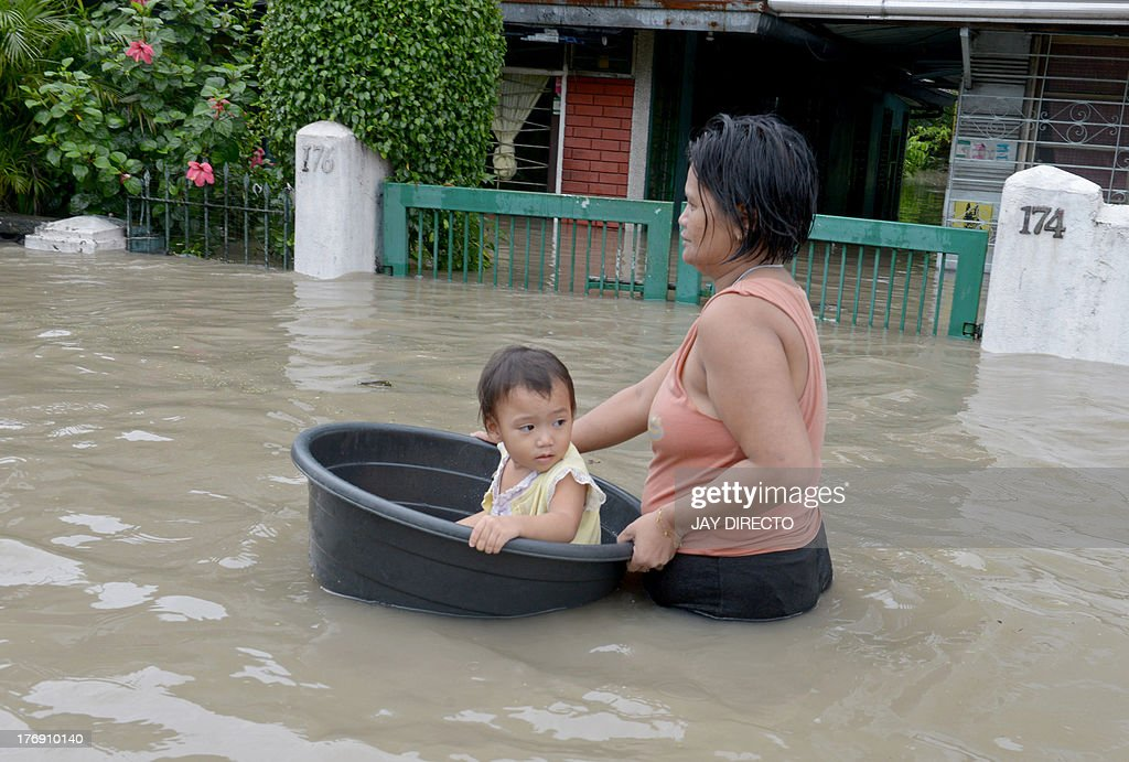 Residents wade through floodwaters in the farming town of Novaleta, some 26 kilometres outside Manila on August 19, 2013. Torrential rain paralysed large parts of the Philippine capital on August 19 as neck-deep water swept through homes, while floods in northern farming areas claimed at least one life. AFP PHOTO / Jay DIRECTO