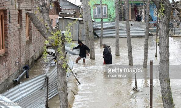 Residents wade through waters towards their home in a neighbourhood of Srinagar on March 30 2015 At least 10 people have been buried by mudslides and...