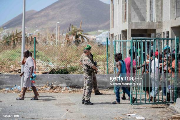 Residents wait a distribution of food and water in front of Saint Martin III's College in the Orleans neighborhood eleven days after the passage of...