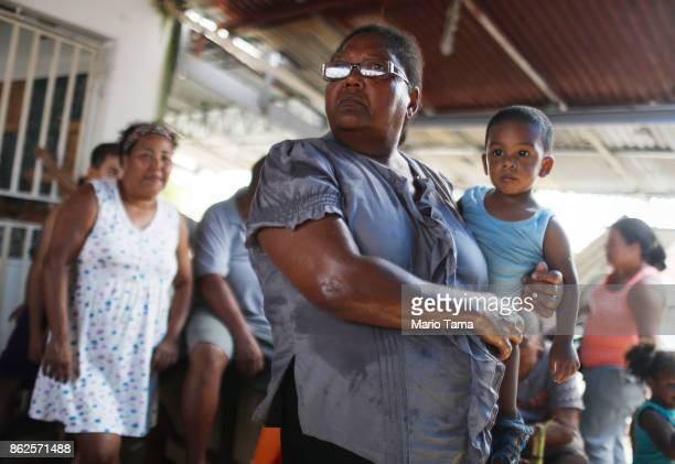 Residents wait in the shade for food and water aid provided by FEMA to arrive in a neighborhood without grid electricity or running water on October...