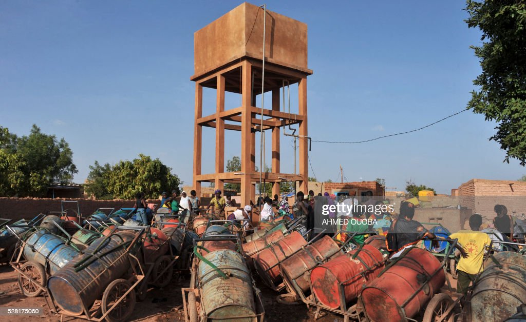 Residents wait next to canisters used to collect water in the poor district of Taptenga suburb of Ouagadougou on May 4, 2016. Burkina Faso will impose restrictions on water supplies in the capital Ouagadougou next week to tackle a serious shortage in the city of two million, officials said. / AFP / AHMED