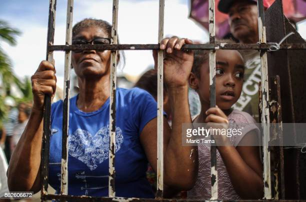 Residents wait to receive food and water provided by FEMA in a neighborhood without grid electricity or running water on October 17 2017 in San...