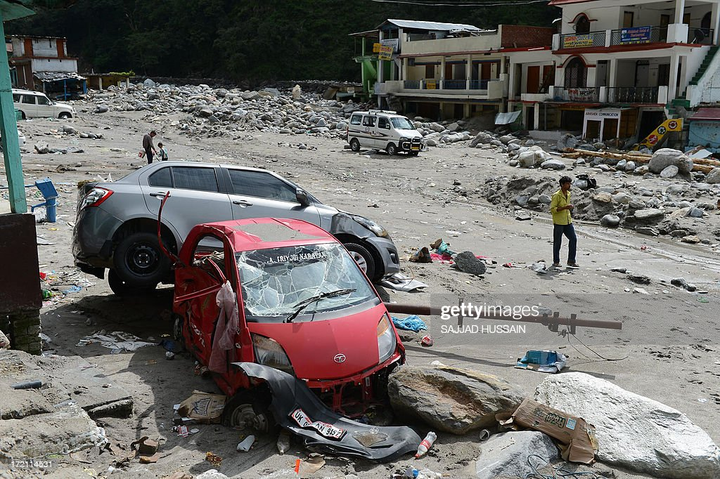 Residents walk beside the wreckage of vehicles in Sonprayag on July 2, 2013, in a flood affected area of the northern Indian state of Uttrakhand. Construction along river banks will be banned in a devastated north Indian state amid concerns unchecked development fuelled last month's flash floods and landslides that killed thousands, the state's top official said. The Chief Minister of Uttarakhand, Vijay Bahuguna, also announced that a regulatory body would be set up to scrutinise future construction as the Himalayan state begins the herculean task of rebuilding following the June 15 floods. AFP PHOTO/SAJJAD HUSSAIN