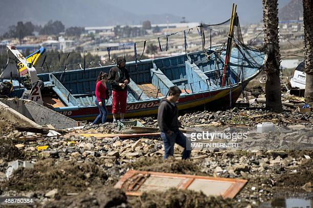 Residents walk between debris caused by the sea in the port of Coquimbo some 445 km north of Santiago during the eve's earthquake on September 17...