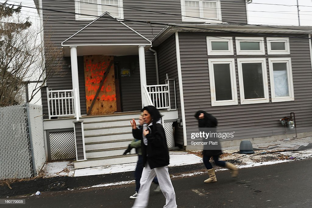 Residents walk by a flood damaged home in Oakwood Beach in Staten Island on February 5, 2013 in New York City. In a program proposed by New York Governor Andrew Cuomo, New York state could spend up to $400 million to buy out home owners whose properties were destroyed by Superstorm Sandy. The $50.5 billion disaster relief package, which was passed by Congress last month, would be used to fund the program. If the program is adopted, homeowners would be relocated and their land would be left as a natural barrier to help absorb future floods waters.