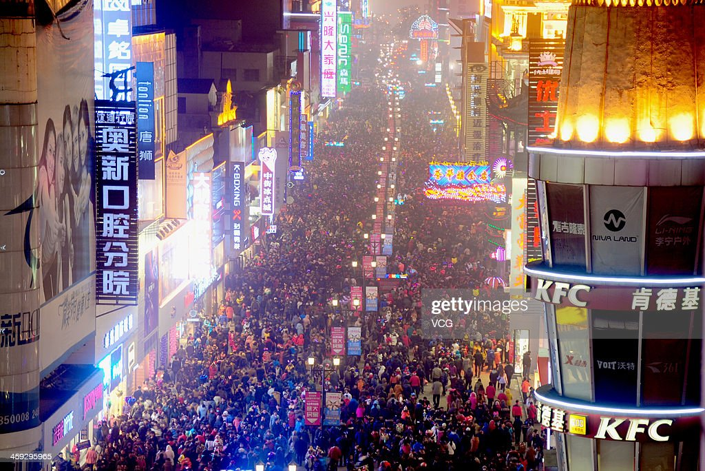 Residents walk in a street attending a celebration of Christmas Eve on December 24, 2013 in Shenyang, China.