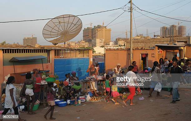 Residents walk in a street in downtown Luanda on January 26 2010 Angola's Africa Cup of Nations squad were awarded 150000 dollars by a bank to reward...