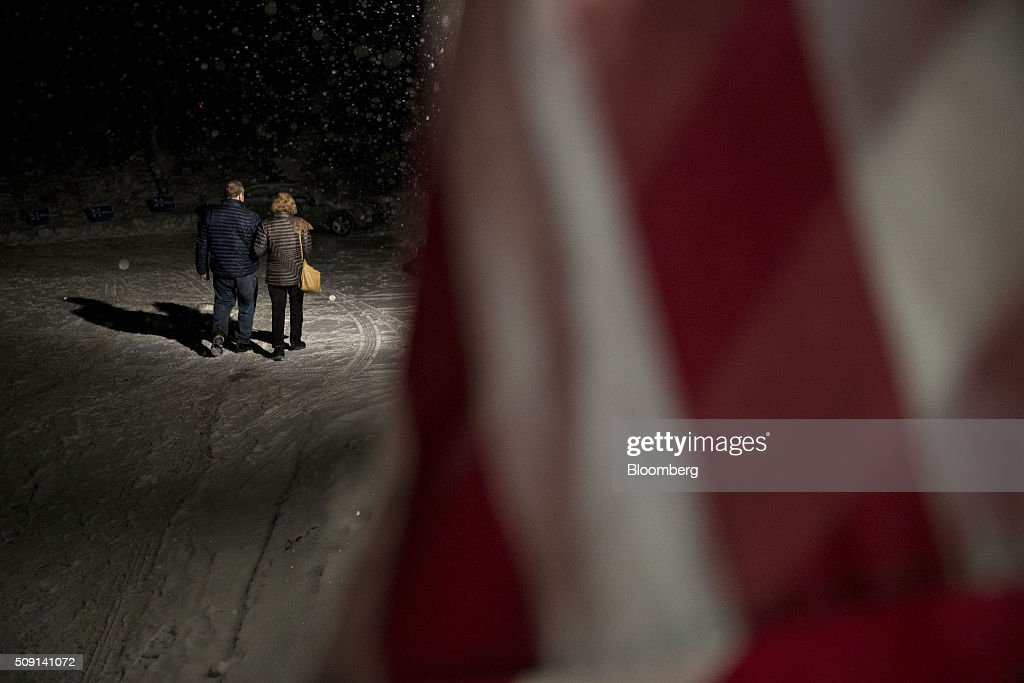Residents walk in the snow after casting their votes in the New Hampshire presidential primary election at the town hall polling site in Harts Location, New Hampshire, U.S., on Tuesday, Feb. 9, 2016. According to the New Hampshire Secretary of State's office, the state has 383,834 voters who haven't declared a party affiliation, compared to 260,896 registered Republicans and 229,202 Democrats. Photographer: Andrew Harrer/Bloomberg via Getty Images