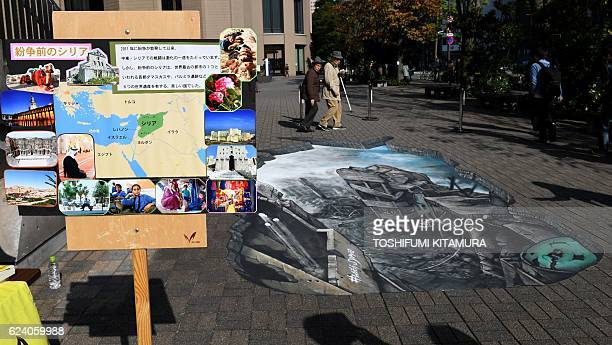 Residents walk near a 3D optical illusion artwork of a devastated cityscape in Aleppo Syria at the campus of the Meiji University in Tokyo on...