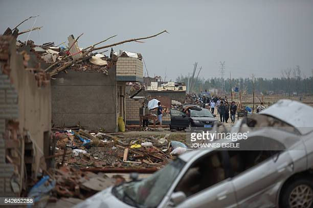 Residents walk next to the rubble of destroyed houses after a tornado in Funing in Yancheng in China's Jiangsu province on June 24 2016 Extreme...