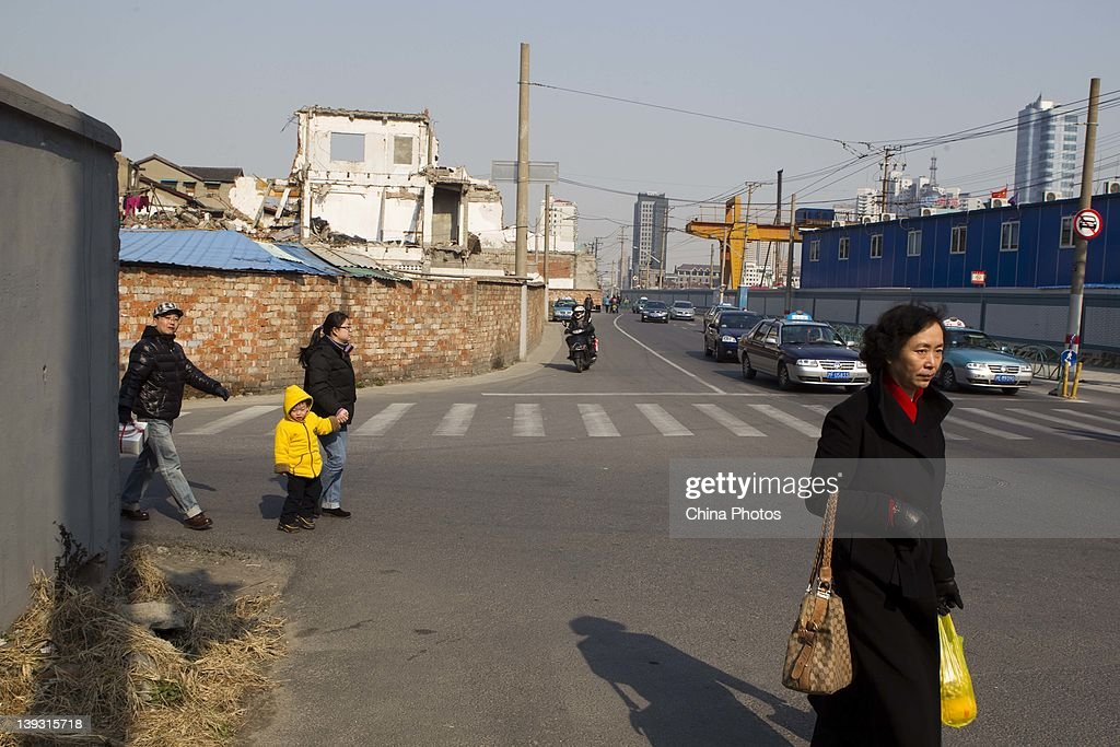 Residents walk on a road at the North Bund on February 19, 2012 in Shanghai, China. According to local media, the North Bund area will be reconstructed as a international shipping and financial zone, a modern commercial and high-end residential area, and recreation center.