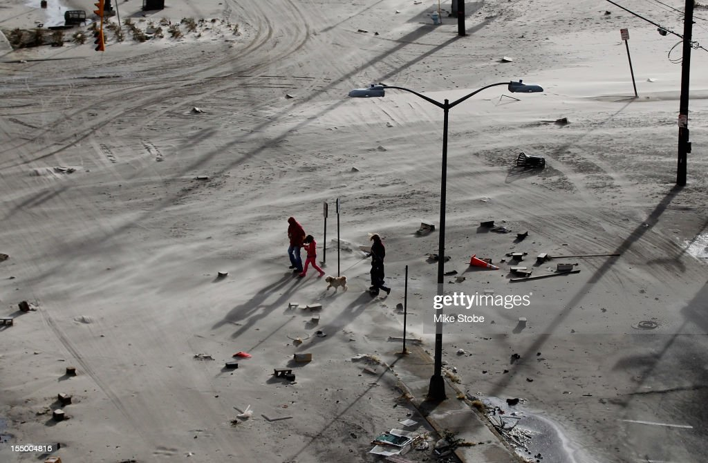 Residents walk on a street covered in beach sand due to flooding from Hurricane Sandy on October 30, 2012 in Long Beach, New York. The storm has claimed at least 33 lives in the United States, and has caused massive flooding across much of the Atlantic seaboard. U.S. President Barack Obama has declared the situation a 'major disaster' for large areas of the U.S. east coast, including New York City, with widespread power outages and significant flooding in parts of the city.
