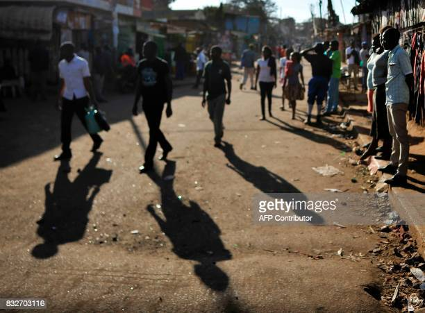 Residents walk on a street in the Kibera district of Nairobi on August 16 2017 in Nairobi's largest slum Kibera as life returns to normal after...