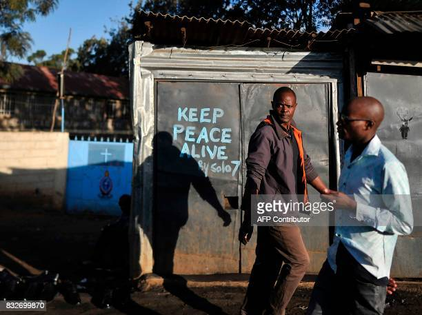 Residents walk past a closed shop with a message calling for peace painted on its doors in the Kibera district of Nairobi on August 16 as life...