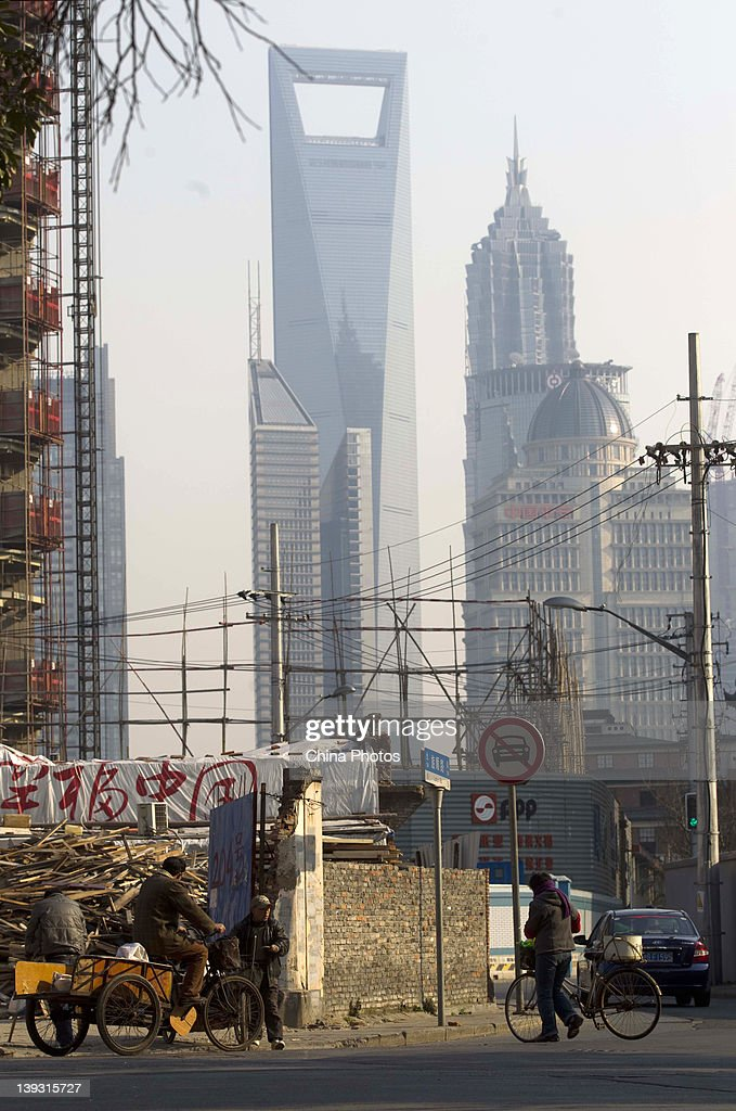 Residents walk past a construction site in the background of skyscrapers in the Lujiazui Financial District at the North Bund on February 19, 2012 in Shanghai, China. According to local media, the North Bund area will be reconstructed as a international shipping and financial zone, a modern commercial and high-end residential area, and recreation center.