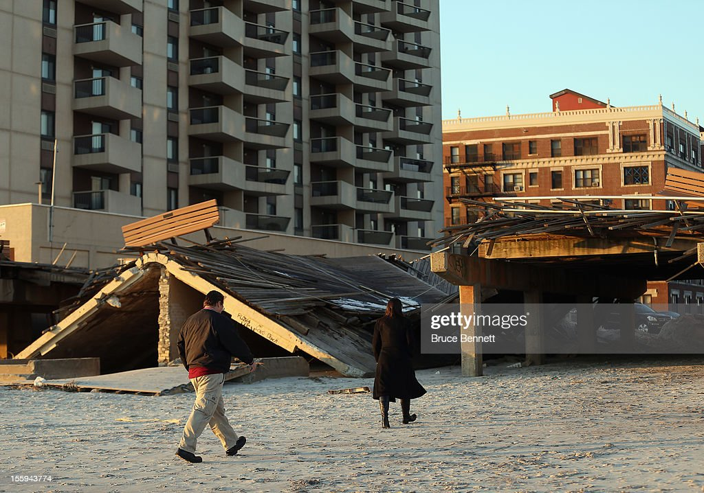 Residents walk past a destroyed section of the boardwalk at the base of Lincoln Boulevard as Long Islanders continue their clean up efforts in the aftermath of Superstorm Sandy on November 9, 2012 in Long Beach, New York. New York Gov. Andrew M. Cuomo has said that the economic loss and damage to homes and business caused by Sandy could total $33 billion in New York, according to published reports.
