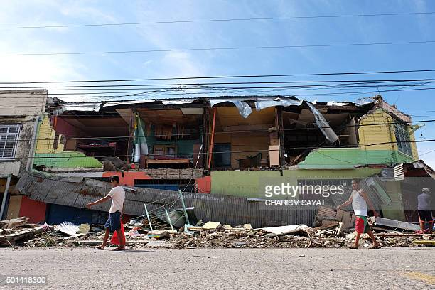 TOPSHOT Residents walk past a house destroyed by typhoon Melor after it hit Bulan town Sorsogon province south of Manila on December 15 2015 Tattered...