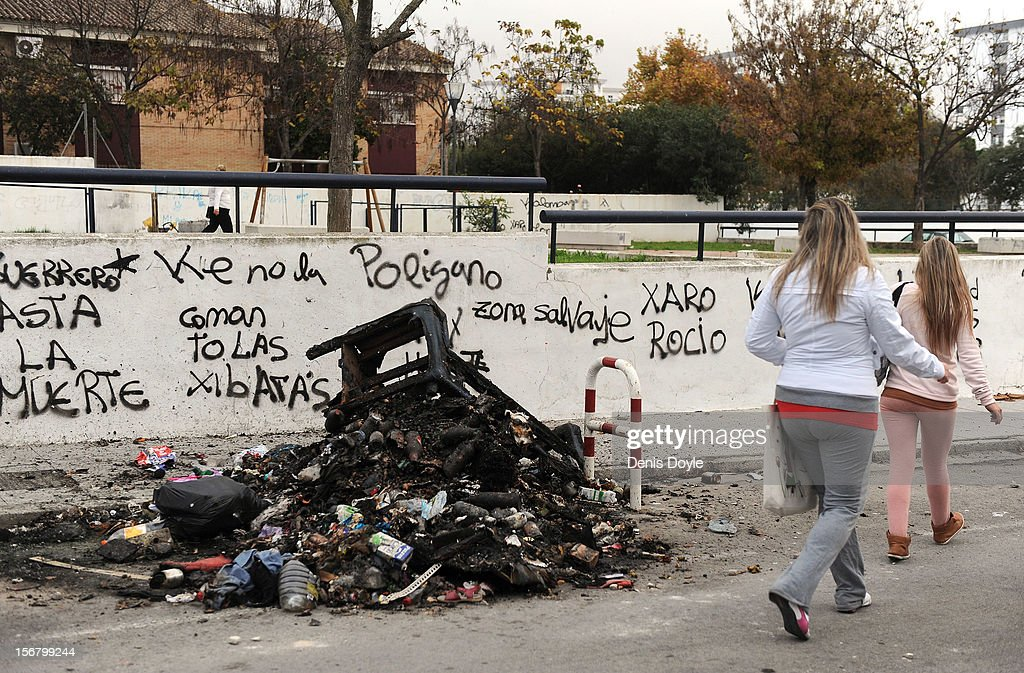 Residents walk past a pile of burnt uncollected garbage during the 20th day of the garbage collectors strike on November 21, 2012 in Jerez de la Frontera, Spain. The garbage collectors are protesting planned layoffs in the sector by the local town council.