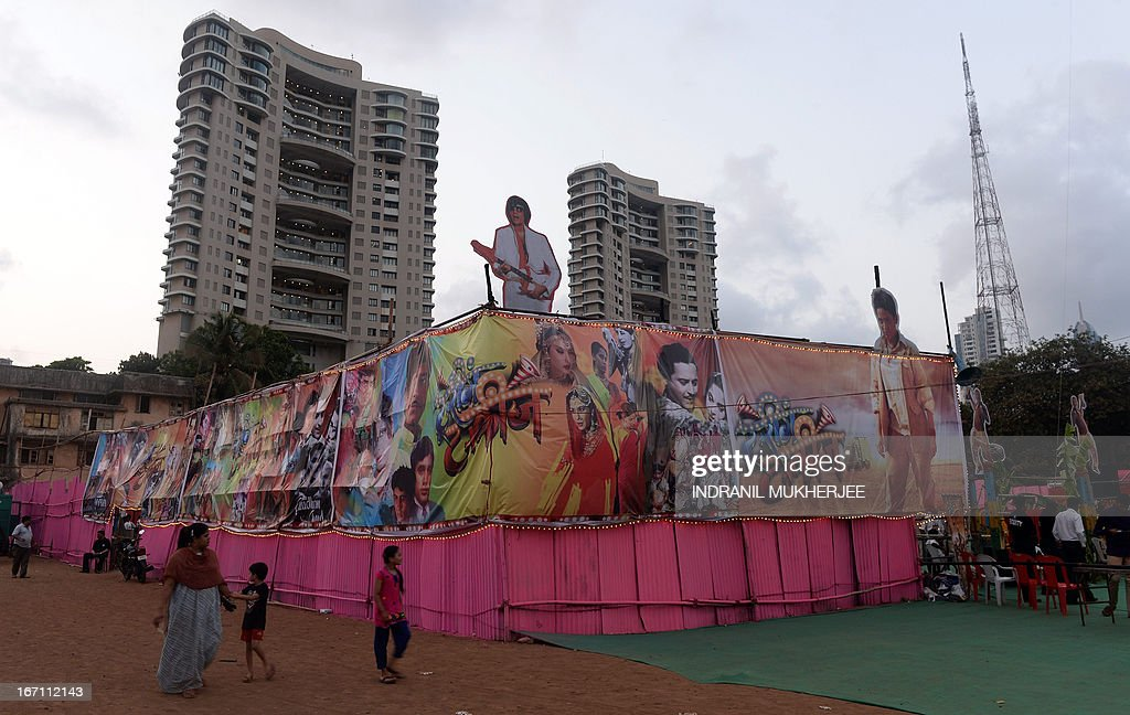 Residents walk past a poster collage of various Indian movies put up to decorate the boundary wall of the Anup Touring Talkies tent cinema at a ground in central Mumbai on April 19, 2013. To mark 100 years of Indian Cinema, a Marathi film 'Touring Talkies' is being screened in a makeshift tent theatre just like the days of yore, in its pre-multiplex and pre-single screen glory dating back 50 years. The tents, keeping in mind modern audiences, will have plush seating, air conditioning and popcorn and cola alongside fresh sugar-cane juice, roasted groundnuts and gram and pickle and other tit-bits. The cinema will screen four shows per day for a week. The idea of touring talkies was the brainchild of the doyne of Indian cinema, Dadasaheb Phalke, after he saw the British watching movies in tents. The touring cinema would travel through rural India and screen movies in makeshifts tents. At present, one can only find these talkies - whose sweltering tents and basic facilities contrast with the plush, air-conditioned multiplexes springing up in Indian cities, during Jatras (village fairs) in the interiors of the state. AFP PHOTO/ INDRANIL MUKHERJEE