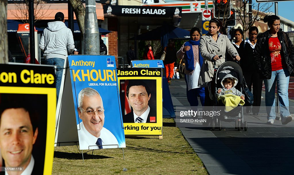 Residents walk past a row of candidates portraits in front of a pre-poll voting center in the Bankstown suburbs of western Sydney on August 21, 2013. Prime Minister Kevin Rudd, who is trailing in the opinion polls to conservative rival Tony Abbott ahead of September 7 elections, has gambled his fortunes on a plan to send boatpeople to Papua New Guinea for processing and resettlement. AFP PHOTO / Saeed Khan
